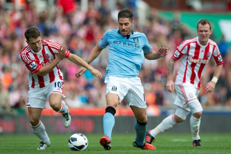 Stoke City's Michael Owen (L) vies for the ball with Manchester City's Javi Garcia (C) during the Premiership football match at The Brittania Stadium in Stoke on September 15, 2012. The game ended 1-1. AFP PHOTO / ADRIAN DENNISRESTRICTED TO EDITORIAL USE Additional licence required for any commercial/promotional use or use on TV or internet (except identical online version of newspaper) of Premier League/Football League photos. Tel DataCo +44 207 2981656. Do not alter/modify photo.
