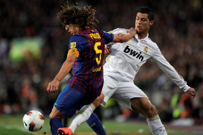 Barcelona's captain Carles Puyol (L) vies with Real Madrid's Portuguese forward Cristiano Ronaldo during the Spanish League