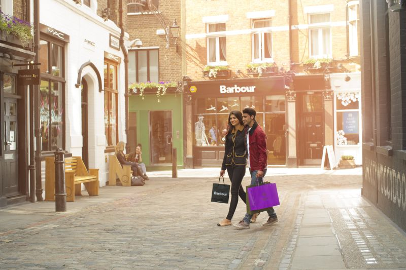 Shopping in London. A sidestreet in a fashionable area of the city lined with designer label clothing shops. Two people carrying shopping bags. Barbour shop. Covent Garden area.