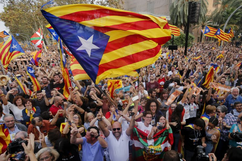 People celebrate after Catalonia's parliament voted to declare independence from Spain in Barcelona on October 27, 2017.  Catalonia's parliament voted to declare independence from Spain and proclaim a republic, just as Madrid is poised to impose direct rule on the region to stop it in its tracks. A motion declaring independence was approved with 70 votes in favour, 10 against and two abstentions, with Catalan opposition MPs walking out of the 135-seat chamber before the vote in protest at a declaration unlikely to be given official recognition.  / AFP PHOTO / PAU BARRENA