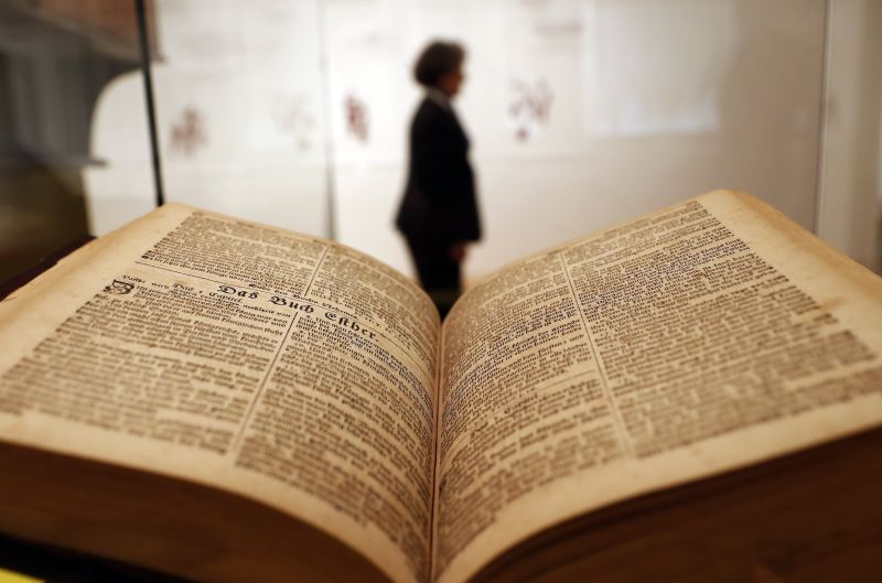 A woman walks past the Sauer Bible in the area dedicated to the United States, as part of the exhibition 'The Luther Effect - 500 Years Protestantism in the World' at the Martin Gropius Bau, Berlin, Germany, 11 April 2017. Including objects from four different continents the show explores the diversity and history of protestantism in the last centuries around the world, highlighting the examples of Sweden, the United States, South Korea, and Tanzania. More than 500 objects are exhibited marking the 500th anniversary of the Reformation.