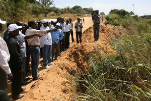 Delegação governamental observando  a ravina que ameaça engolir a aldeia do Tchizo e impede a circulação automóvel naquela área
