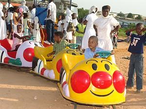 Crianças a divertirem-se no parque de diversões que leva os carrosséis a todo o país