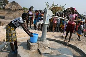 Jovens mulheres da aldeia de Calungulungo retiram água do poço melhorado