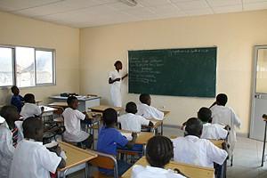 Alunos atentos às explicações da professora durante uma aula na comuna que não tem crianças fora do sistema de ensino