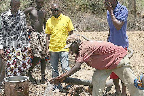 Momento em que o soba Joaquim Munukanheva faz o ensaio do novo furo retirando do poço um volume considerável de água