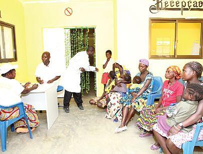 Pormenor do interior do centro de saúde na sede da vila de Luma-Kassai com pacientes a serem assistidos por um dos enfermeiros