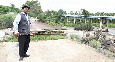 O coronel Trocado mostra a nova ponte sobre o rio Queve ao fundo e em primeiro plano parte daquele que foi à época a maior ponte de Angola