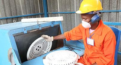 Operador de máquina insere tampa de cesto de roupa no equipamento de reciclagem
