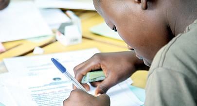 Jovem estudante do ensino secundário preenche a ficha de confirmação de matrícula com o dinheiro à vista para proceder ao pagamento