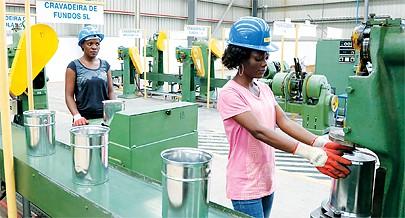As operadoras de máquinas têm como trabalho criar molduras para as latas usadas para acondicionar tintas e diluentes
