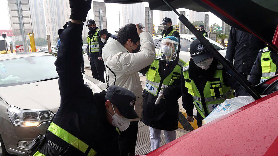 Agentes com máscaras inspecionam carro e homem em rua da cidade de Xianning
