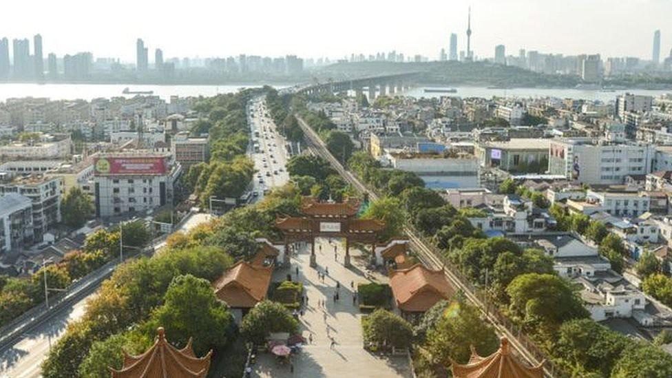 Imagem aérea de Wuhan durante o dia, na qual se pode ver ponte, prédios e portal tradicional chinês