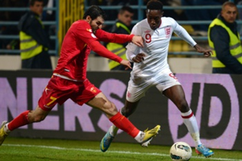 Montenegro's midfielder Simon Vukcevic (L) vies for the ball with England's forward Danny Welbeck (R) during their World Cup 2014 qualification match at Podgorica stadium in Podgorica on March 26, 2013. AFP PHOTO / DIMITAR DILKOFF