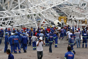 "Workers stare at damages after a crane fell across part of the metallic structure at the Arena de Sao Paulo --Itaquerao do Corinthians-- stadium, still under construction, on November 27, 2013 in Sao Paulo. Two people died and another was injured following the accident on the stadium that will host the opening match of Brazil 2014 FIFA World Cup. AFP PHOTO/LANCEPRESS - EDUARDO VIANA == RESTRICTED TO EDITORIAL USE - MANDATORY CREDIT ""AFP PHOTO/LANCEPRESS - EDUARDO VIANA"" - NO MARKETING NO ADVERTISING CAMPAIGNS - DISTRIBUTED AS A SERVICE TO CLIENTS =="