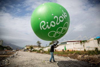 epaselect epa04341989 A worker carries huge balloons next to the Olympic Park in Barra two years prior to the Rio2016 Olympic Games, in Rio de Janeiro, Brazil, 05 August 2014. The balloons mark the locations in the City where the different stadiums will be built. EPA/MICHAEL KAPPELER