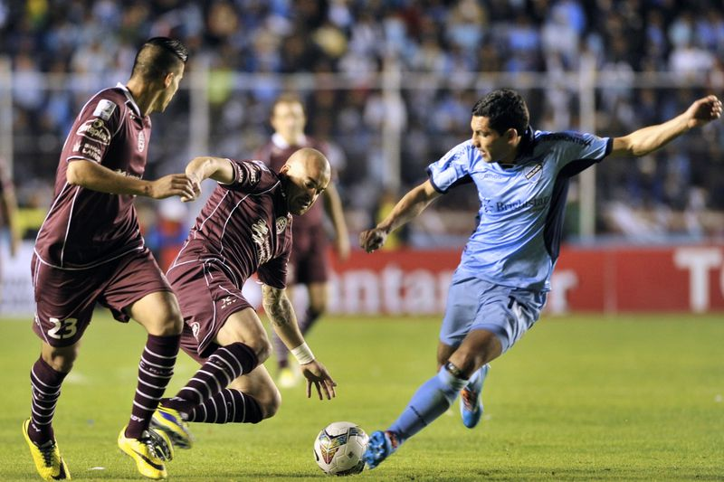 Oscar Benitez interessa a Jesus • Footballers Oscar Benitez (L), and Santiago Silva (C), of Lanus of Argentina, vie for the ball Walter Flores (R) of Bolivia's Bolivar, during a Libertadores Cup football football match held at the Hernando Siles Stadium in La Paz on May 15, 2014. AFP PHOTO/Aizar Raldes • AFP