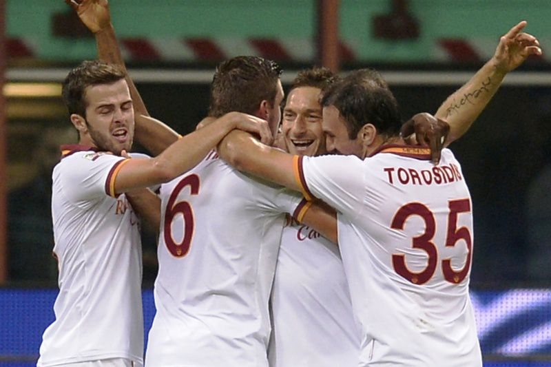 AS Roma's forward Francesco Totti (C) celebrates with teammates after scoring against Inter Milan during their Serie A football match on October 5, 2013 in Milan.  AFP PHOTO / ALBERTO LINGRIA