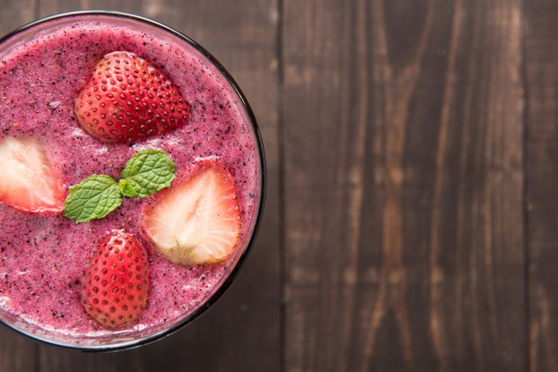 Strawberry smoothie in glass on wooden background