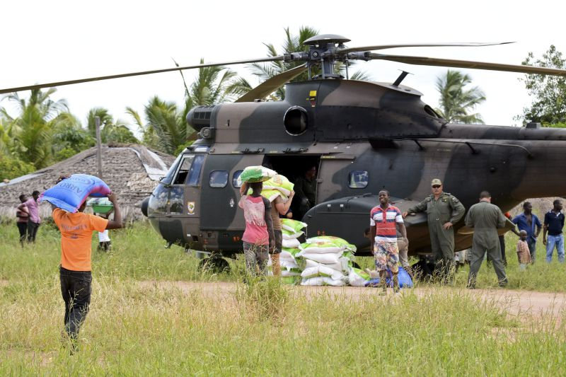 epa04587050 A helicopter from the South Africa Air Force delivers supplies for the flood displaced people in Mocuba, Zambezia province, Mozambique, 26 January 2015. The floods in Zambezia province affect presently 124 000 people and have caused 79 deaths up to now.  EPA/ANTONIO SILVA