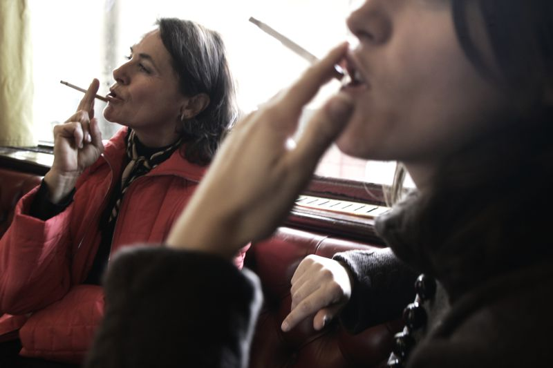 FRANCE, Rennes : Two women smoke cigarettes in a bar 13 January 2006 in Rennes. The French government is studying the feasibility of a total ban on smoking in public spaces after an official report concluded that existing restrictions are not functioning properly. AFP PHOTO FRED DUFOUR