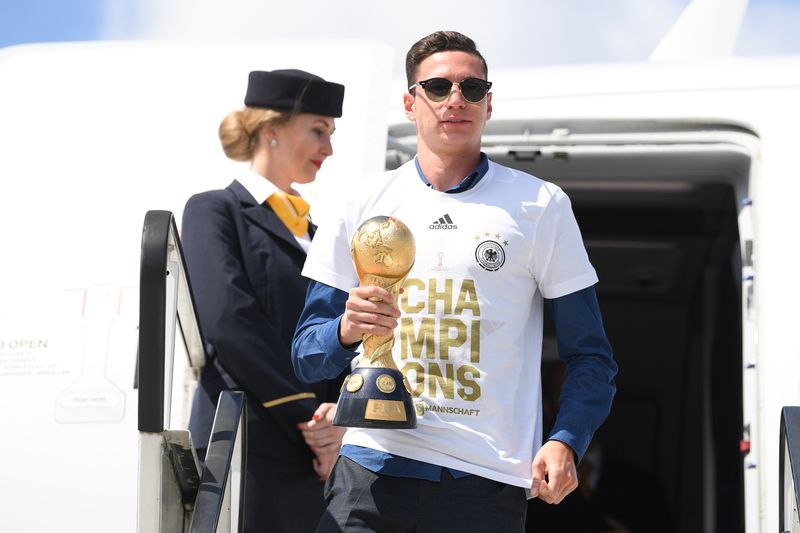 Julian Draxler sai do avião com a Taça das Confederações • Julian Draxler, captain of the German national football team, holds the trophy as he and his teammates leave the plane after arriving at the airport in Frankfurt am Main, western Germany, on July 3, 2017, one day after they won the 2017 Confederations Cup football tournament.  • Arne Dedert / dpa / AFP