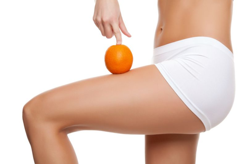 Woman with an orange showing a perfect skin without cellulitis