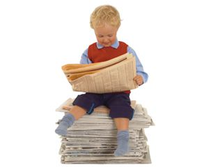 Boy Sitting on Newspapers Reading Newspaper --- Image by © Creasource/Corbis