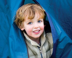 A young boy emerges from a tent on a camping trip