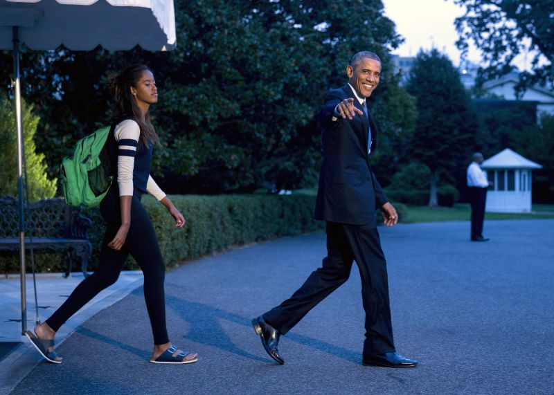 epa04408366 US President Barack Obama (R) gestures as he and his daughter Malia Obama walk out of the White House to board a Marine One on the South Lawn in Washington, DC, USA, 19 September 2014. The First Family is traveling to Camp David for the weekend and is expected to return to the White House on 21 September.  EPA/ANDREW HARRER/POOL