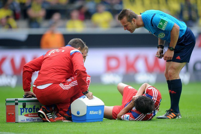 Javi Martinez lesionado na Supertaça da Alemanha • Munich's Javi Martinez lies on the ground with an injury, while a helper and referee Peter Gagelmann (R) stand next to him during the DFL Supercup soccer match Borussia Dortmund vs FC Bayern Munich at Signal Iduna Park in Dortmund, Germany, 13 August 2014. (ATTENTION: Due to the accreditation guidelines, the DFL only permits the publication and utilisation of up to 15 pictures per match on the internet and in online media during the match.) • EPA/Rolf Vennenbernd EPA/JONAS GUETTLER