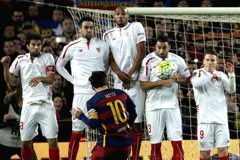 Lionel Messi remate num livre direto • epa05185613 FC Barcelona's Argentinian striker Lionel Messi (front) takes a free kick to score the 1-1 equalizer against Sevilla FC during the Spanish Liga Primera Division soccer match played at Camp Nou stadium in Barcelona, Spain, 28 February 2016.  • EPA/Alberto Estevez
