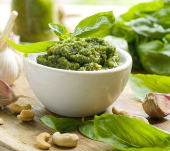 Basil pesto in a small bowl, with fresh basil leaves