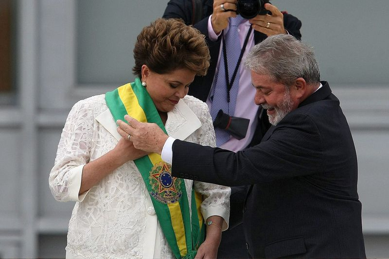 Dilma e Lula • epa05215413 (FILE) A file picture dated 01 January 2011 of then Brazilian President Dilma Rousseff (L) receiving congratulations by outgoing President Luiz Inacio Lula da Silva (R) at the Planalto Palace in Brasilia, Brazil, 01 January 2011. Brazilian President Dilma Rousseff on 16 March 2016 named political mentor and predecessor Luiz Inacio Lula da Silva, who is currently battling corruption allegations, as her new Chief of Staff. Lula's appointment as chief of staff changes his legal status and ensures that he can only be tried by the Supreme Court under the shadow of illicit enrichment, money laundering and document falsification allegations that led state prosecutors in Sao Paulo to seek his preventative arrest on 04 March.  EPA/MARCELO SAYAO *** Local Caption *** 02512604