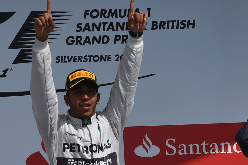 Lewis Hamilton • Mercedes-AMG's British driver Lewis Hamilton celebrates on the podium after winning the British Formula One Grand Prix at the Silverstone circuit in Silverstone on July 6, 2014. AFP PHOTO / DIMITAR DILKOFF • AFP