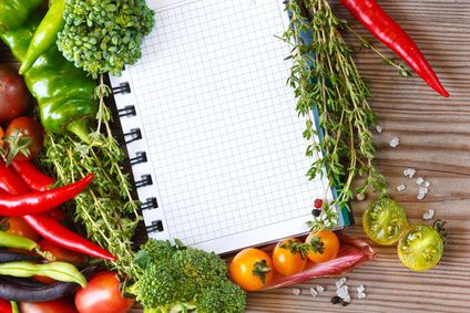 Open notebook and fresh vegetables on an old wooden board.