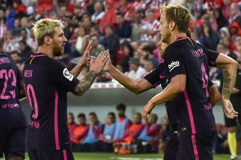 Ivan Rakitic (D) e Leo Messi (E) celebram o golo do Barcelona • epa05513395 FC Barcelona's Croatian midfielder Ivan Rakitic (R) jubilates with Argentinian striker Leo Messi (L) and defender Jordi Alba (2R) after scoring a goal against Athletic Bilbao during their Primera Division soccer match played at San Mames stadium in Bilbao, Basque Country, Spain on 28 August 2016.  • EPA/MIGUEL TONA