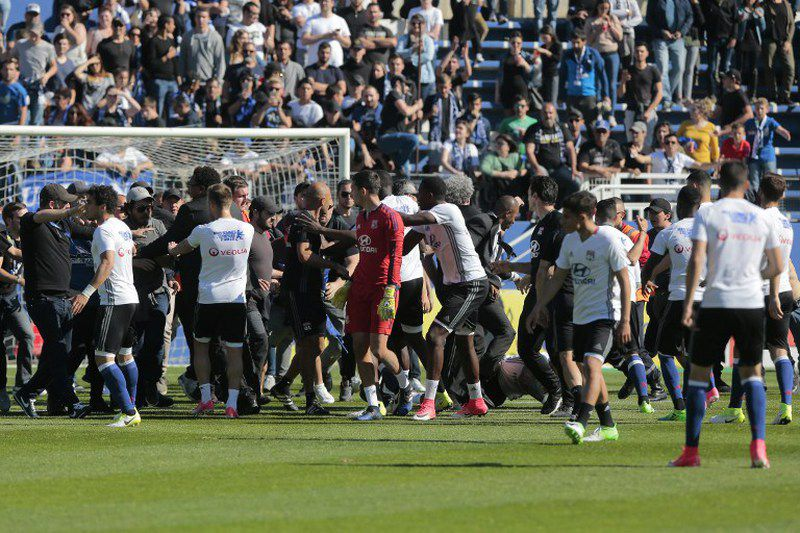 Adeptos do Bastia invadem o campo • Stewards and Lyon staff members try to stop Bastia's supporters who invade the pitch to fight with Lyon players during warm up prior to the French L1 Football match between Bastia (SCB) and Lyon (OL) on April 16, 2017, at the Armand Cesari stadium, in Bastia, on the French Mediterranean island of Corsica.  • PASCAL POCHARD-CASABIANCA / AFP