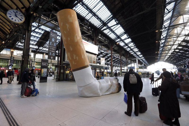 FRANCE, Paris : People pass by a giant mock-up discarded cigarette displayed on the ground at the Gare de Lyon railway station in Paris, on December 4, 2012, as part of a public-awareness campaign launched by France's national rail company SNCF to shed light on commuters' disrespectful behaviour. AFP PHOTO PIERRE VERDY