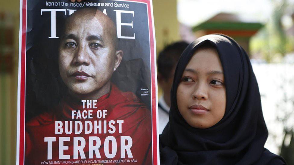 Um manifestante segura uma faixa que diz 'A Face do Terror Budista' com a imagem de Wirathu durante uma manifestação em Jacarta