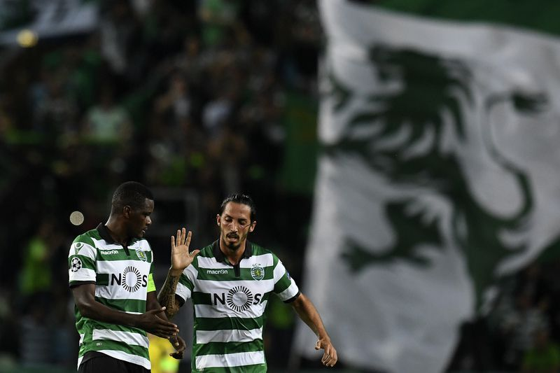 William Carvalho festeja um golo do Sporting diante do Borussia Dortmund com Ezequiel Schelotto. • EPA/Francisco Leong