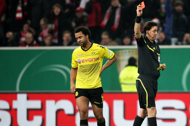 Dortmund's defender Patrick Owomoyela (L)  reacts after receiving a red card from referee Manuel Gr