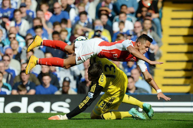 Courtois lesiona-se no encontro entre o Chelsea e o Arsenal • Thibaut Courtois (down) in action against Arsenal's Alexis Sanchez during the English Premier League soccer match between Chelsea FC and Arsenal FC at Stamford Bridge in London, Britain, 05 October 2014.  • EPA/FACUNDO ARRIZABALAGA