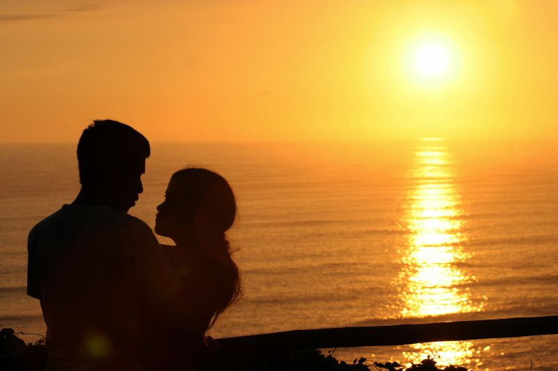 A young couple have a cuddle while watching the sunset in the