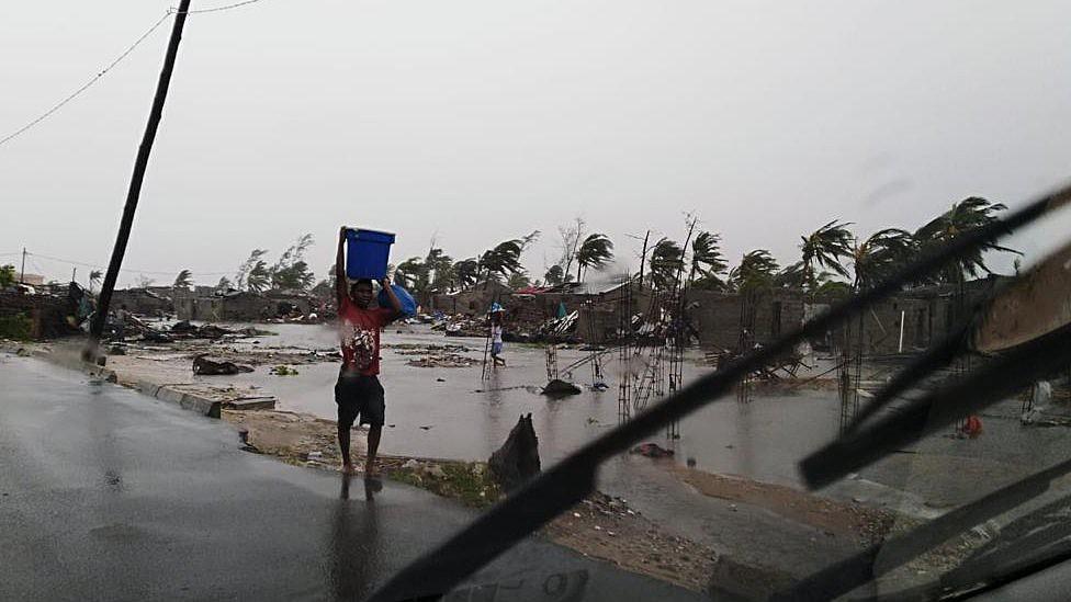 Menino carrega balde em meio à destruição em Beira