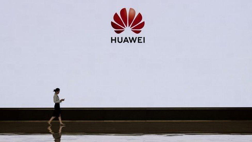 Mulher passa pela logo da Huawei
