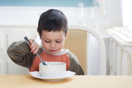 Small child boy eating a soup in a restaurant.