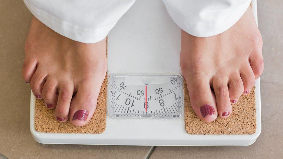 Mulher se pesa na balança
