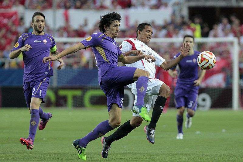 Carlos Bacca e Stefan Savic disputam a bola • epa04737385 Sevilla FC's Colombian striker Carlos Bacca (R) fights for the ball with Montenegrinian defender Stefan Savic (2L) of ACF Fiorentina during the first Europa League match played between Sevilla FC and ACF Fiorentina played at Ramon Sanchez Pizjuan stadium in Seville, Andalusia, Spain on 07 May 2015.  • EPA/PACO PUENTES