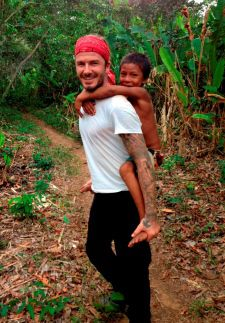Picture shows: David Beckham in the Amazon Rainforest with child from local tribe.